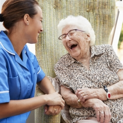 Senior Woman Sitting In Chair And Laughing With Nurse In Retirement Home