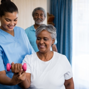 Nurse guiding senior woman in lifting dumbbell at retirement home